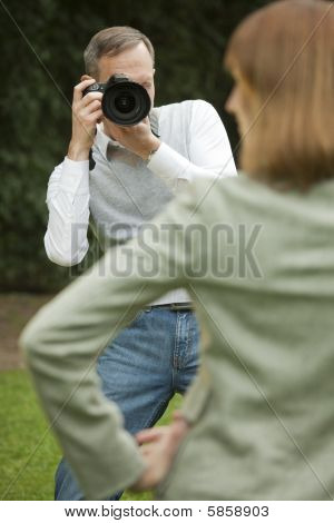 Male Photographer Takes A Picture From Model