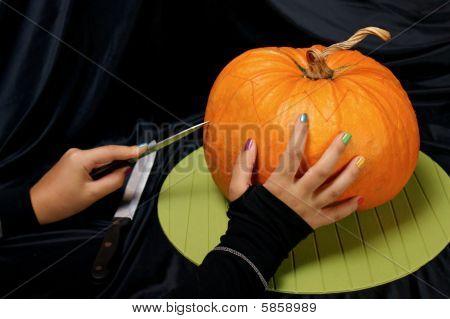Girly Hands Cutting A Halloween Pumpkin