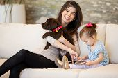picture of puppies mother dog  - Cute young mom spending time with her daughter and a puppy - JPG