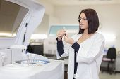 stock photo of centrifuge  - Young woman researching in the medical laboratory - JPG