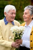 stock photo of elderly couple  - Romantic elderly couple with a bunch of flowers - JPG