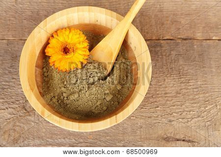 Dry henna powder in bowl on wooden table
