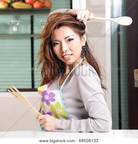 Happy Asian Woman Cooking In The Kitchen