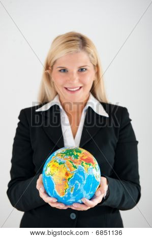 Young business woman holding blue globe