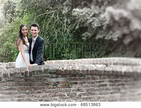 Romantic happy smart young couple on an old stone bridge leaning on the parapet smiling at the camera against greenery