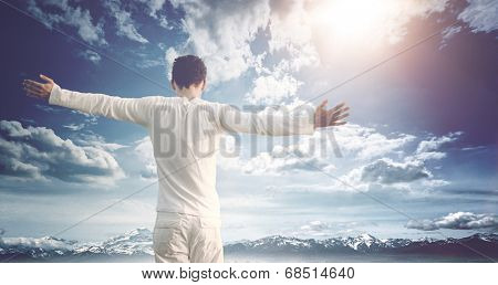 Man celebrating nature and his freedom standing with his back to the camera with wide outspread arms against a blue cloudy sky over snowy mountains with a bright sunburst and lens flare