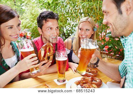 Group of happy friends talking in beer garden in summer in Bavaria