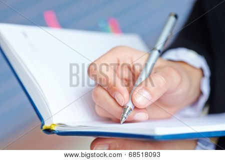 Female hand writing in notebook