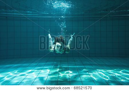 Athletic swimmer smiling at camera underwater in the swimming pool at the leisure centre