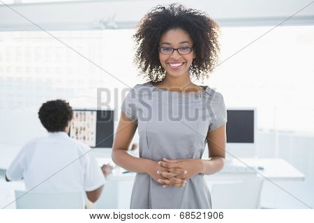 Young pretty editor smiling at camera with colleague working behind her in creative office