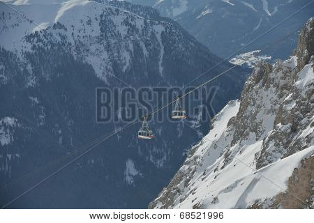 winter landscape with ski chairlift cabin and mountain covered with snow at sunny day