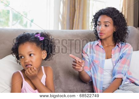 Pretty mother sitting on couch scolding petulant daughter at home in the living room