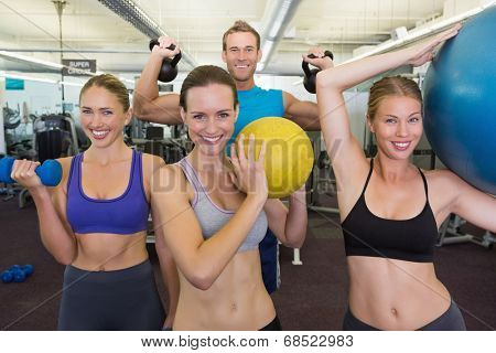 Fitness class posing with different equipment at the gym