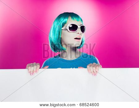 Trendy beautiful young modern woman with green hair wearing stylish sunglasses holding a blank sign with copyspace for your text over a magenta background, looking away