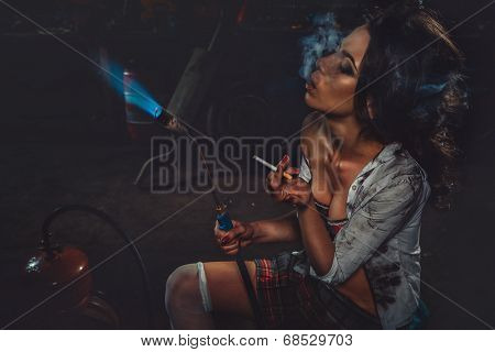 Girl with blowpipe smoking in a garage