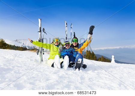 Excited parents and kid in ski masks sit on snow