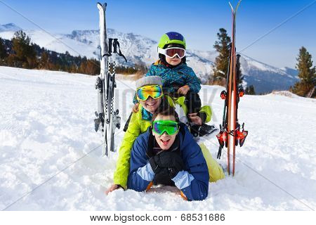 Family in ski masks laying and kid on shoulders