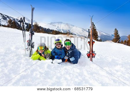 Happy family in ski masks laying on snow