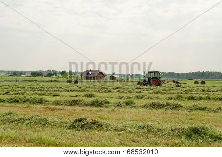 Tractor Turning Raking Cut Hay In Field