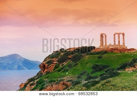 Temple of Poseidon on green hill near sea, Greece