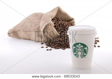 Ankara, Turkey - June 07, 2012:  Cup of Starbucks coffee with cup sleeve in front of sack of coffee beans isolated on white background