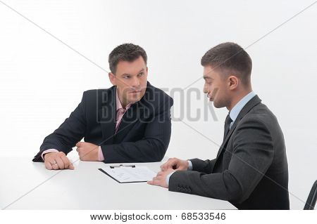 Two business people in elegant suits, chief and employee, holdin