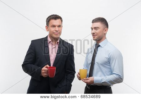 Senior and junior business people discuss something during coffe