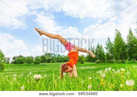 Little girl doing gymnastics on grass