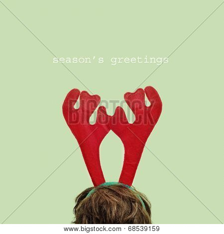 someone wearing a reindeer antlers headband and the sentence seasons greetings in a green  background