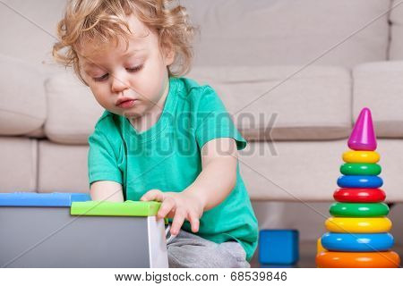 Little Boy Concentrated On Playing With Toys