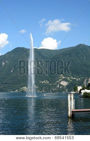 PARADISO, SWITZERLAND - JULY 5, 2014: Monte Sighignola rises behind the fountain in Lake Lugano. Despite being surrounded by Lugano, Paradiso is independent of the larger city.
