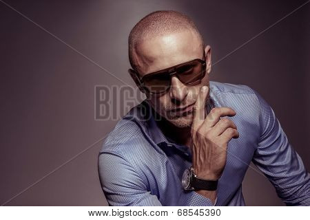 Suave handsome man in sunglasses with his hand to his cheek looking at the camera with a serious expression, on grey with copyspace