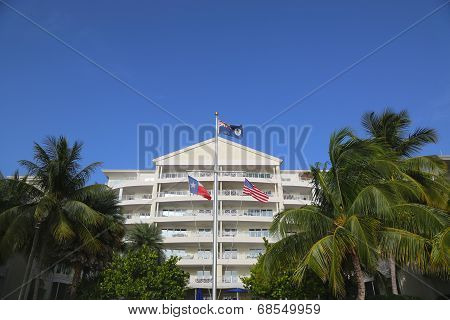 Cayman Islands, United States and State of Texas flag in the front of luxury resort at Grand Cayman