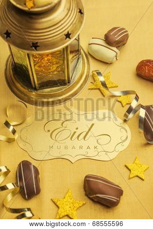 A golden plaque with 'Eid Mubarak' message. A set up with arabic lantern and date chocolates