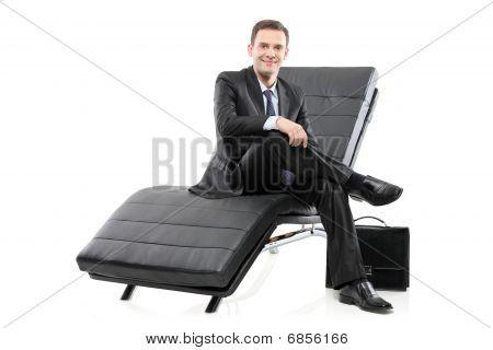 A businessman sited on a sofa