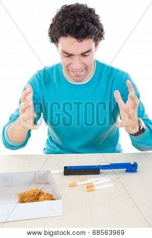 Angry Man Making Cigarettes With Device For Cigar And Dry Tobacco On Table