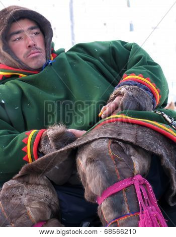 Nadym, Russia - March 11, 2005: Unknown Man Nenets Closeup, Sits On A Snowmobile And Eats.