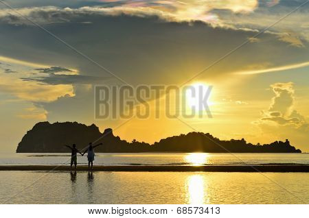 Two Children Standing On The Beach Watching The Sunrise
