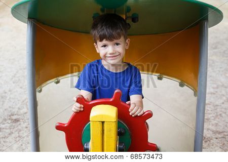 Little Boy As Helmsman On Playground