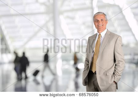 Mature businessman in airport concourse with blurred travellers in background. Man has hands in his pockets and is smiling. Horizontal Format