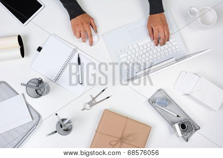 High angle shot of a woman working from her home office. Only her hands are visible as she types on her laptop computer. The white desk is neat with white and silver items.