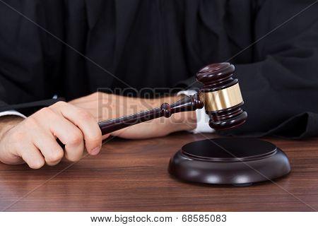 Judge Striking Gavel On Block At Desk