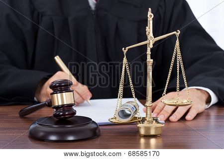 Male Judge Signing Document In Courtroom