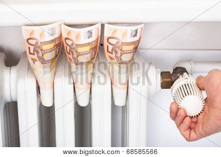 Euro Banknotes By Man Adjusting Thermostat