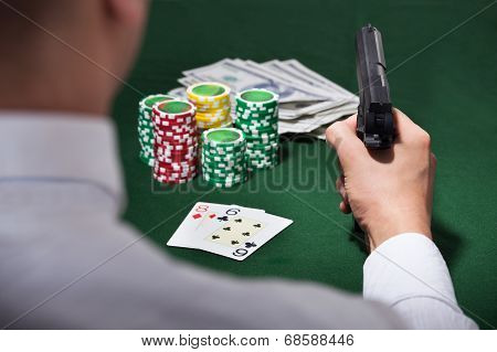 Man Playing Poker While Pointing Gun