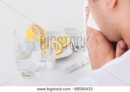 Man Suffering From Cold With Medicines And Water Glass On Table