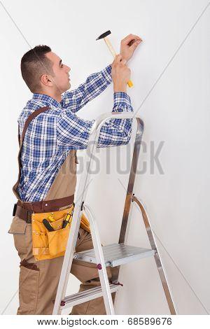 Repairman Hammering Wall With Nail