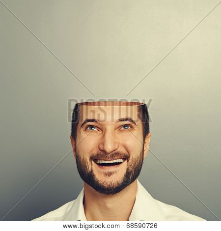 happy young businessman with open head looking up and smiling over grey background