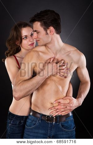 Woman Seducing Man Over Black Background