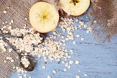 stock photo of sackcloth  - Apple with oatmeal and vintage spoons on sackcloth - JPG